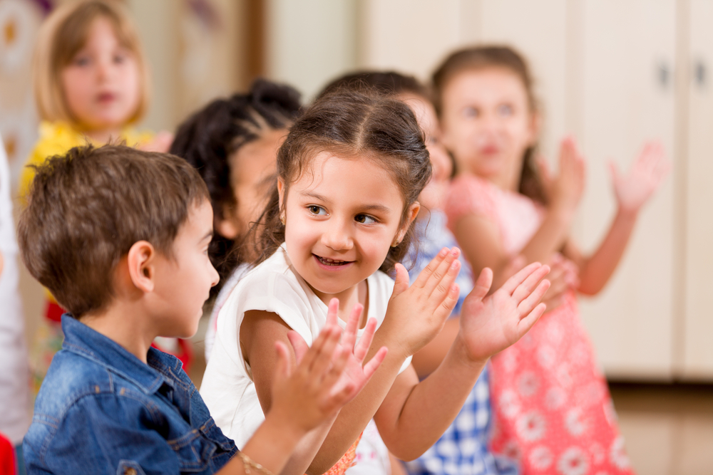 Group of preschool aged children clapping.