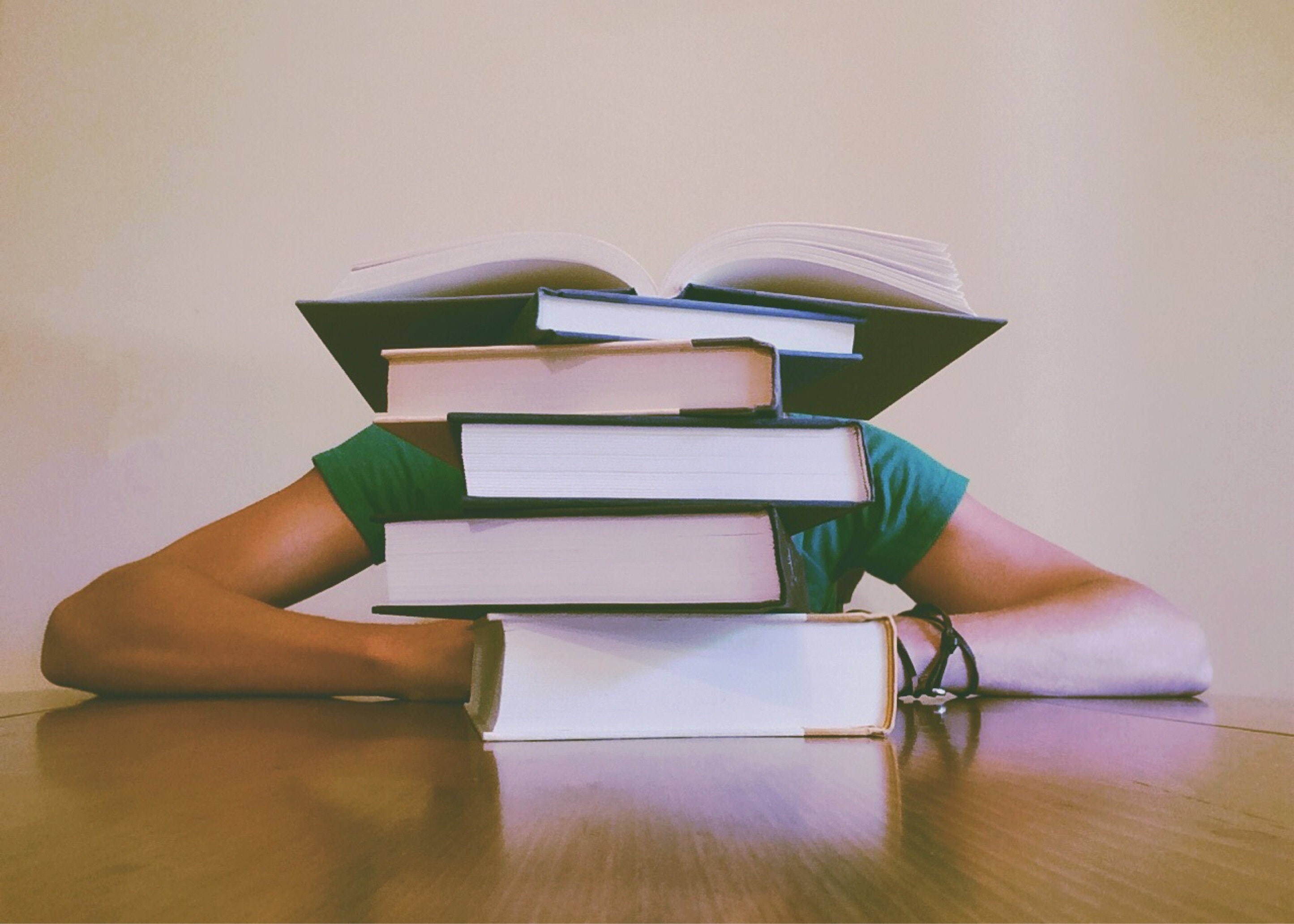 College student behind a pile of books on a desk.