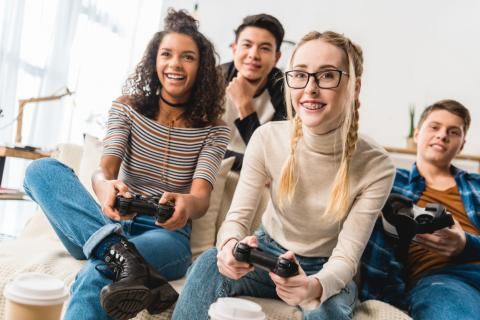 Two teenage girls and two teenage boys playing video games together.