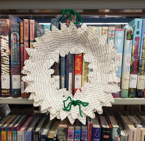 Wreath with leaves made from old book pages hanging off bookshelf